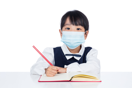 Asian Little Chinese girl writing homework with protection mask in isolated white background