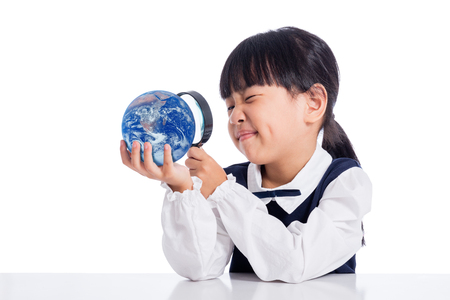 Asian Little Chinese Girl Looking At Globe Through Magnifying Glass in isolated White Background 스톡 콘텐츠