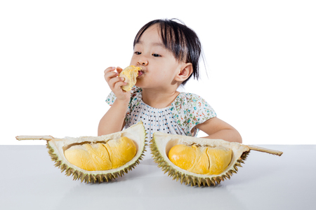 Asian Chinese little girl eating durian fruit in isolated white background