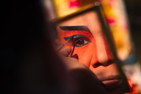 A member of a Chinese Opera group is reflected on a mirror as she prepares at backstage for a performance in Tanjung Sepat, Selangor, Malaysia on Wednesday, Jul. 19, 2017. 