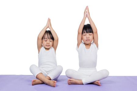 Asian Chinese little girls practicing yoga pose on a mat indoor