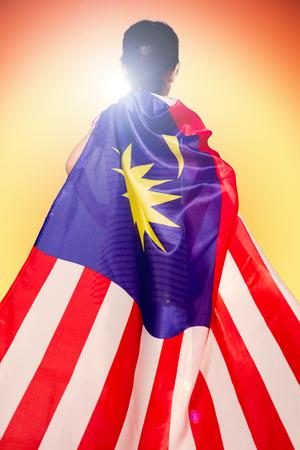 Aziatisch Chinees meisje met Maleisische Vlag op achtergrond van zonsondergang