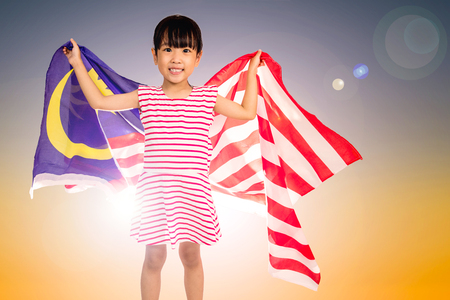 Asian Chinese little girl with Malaysian Flag on background of sunset