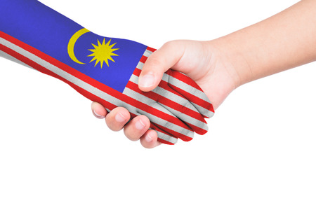 Handshake between a child and Malaysia with flags painted on hand in isolated white background