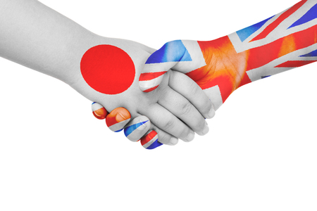Handshake between Japan and United Kingdom with flags painted on childs hands in isolated white background