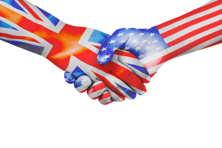 Handshake between United States of America and United Kingdom with flags painted on childs hands in isolated white background Stock Photo