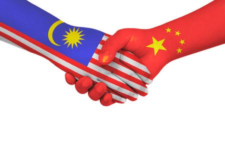 孤立した白い背景の子供の手に描かれたフラグと中国とマレーシア間のハンドシェイク