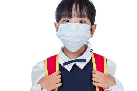 Aziatisch Chinees schoolmeisje met schooltas en het dragen van masker op geïsoleerde witte achtergrond