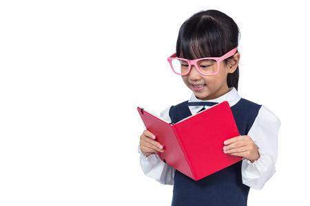 diligente: Pequeña niña asiática de la escuela primaria en uniforme leyendo el libro en fondo blanco aislado Foto de archivo