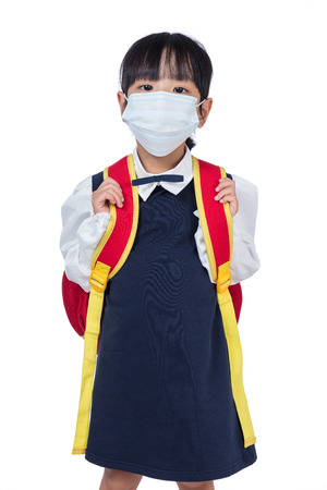 Asian Chinese school girl with school bag and wearing mask in isolated white background