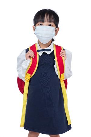 Colegiala china asiática con bolso de escuela y máscara que lleva en fondo blanco aislado Foto de archivo - 83914100