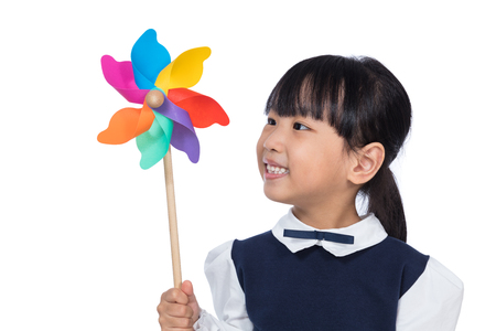 Asian Little Chinese Girl Playing Colorful Pinwheel in isolated White Background