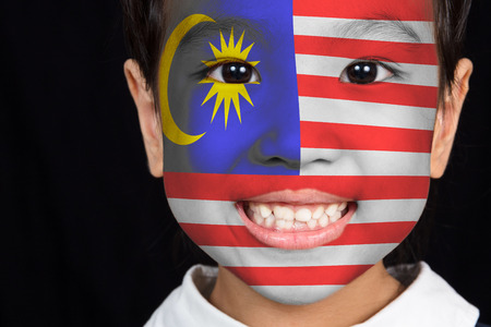 Asian chinese little girl with Malaysian flag on the face in isolated black background Banque d'images