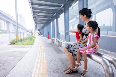 Asian Chinese mother and daughters waiting for a bus at bus stop