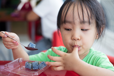 Asian little Chinese girl eating glutinous rice in outdoor restaurant