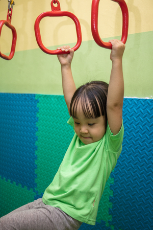 Asian Chinese little girl hanging on rings at indoor playground