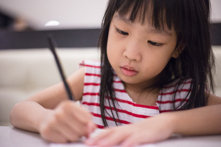 Asian Chinese little girl drawing on paper in restaurant