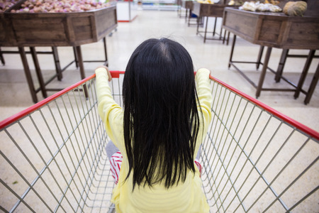 supermarket: Asian Little Chinese Girl sitting in shopping cart in supermarket