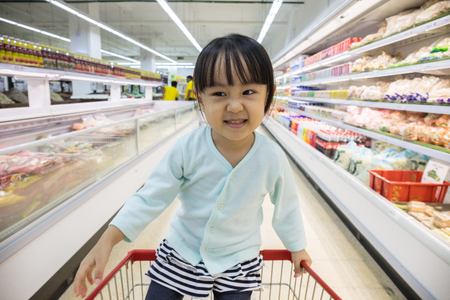 supermarket: Happy Asian Little Chinese Girl sitting in shopping cart in supermarket