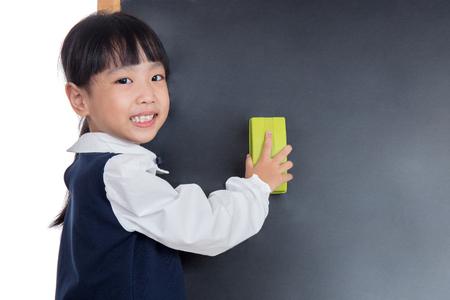 孤立した白い背景に黒板を拭くアジア中国少女