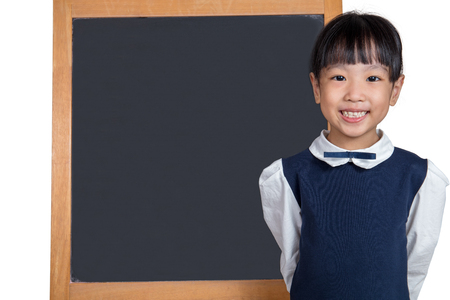 Asian Chinese little girl standing in front of blackboard in isolated white background
