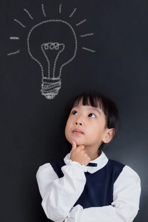 Asian Chinese little girl thinking with bulb sketch on blackboard in isolated black background