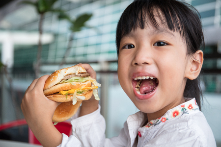Asian Chinese little girl eating burger at outdoor cafe