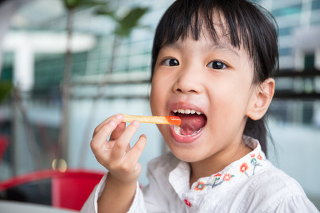 Asian Chinese little girl eating French Fries at outdoor cafe Stock Photo