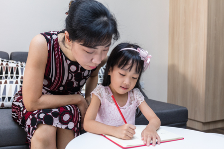 Asian Chinese mother teaching daughter doing homework at home