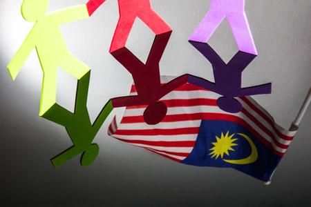 manos unidas: Gente de papel de pie juntos y de la mano bajo la bandera de Malasia