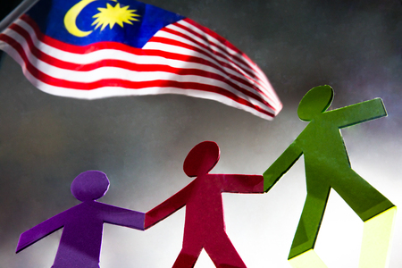 Paper people standing together and holding hands under Malaysian flag