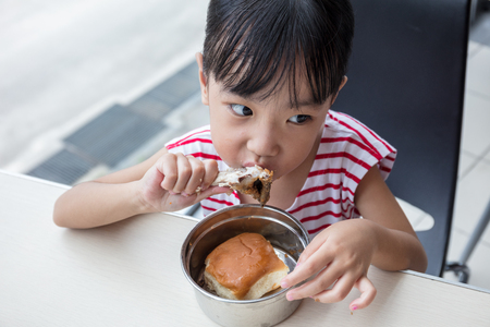 Asian Chinese little girl eating fried chicken at indoor restaurant Stock Photo