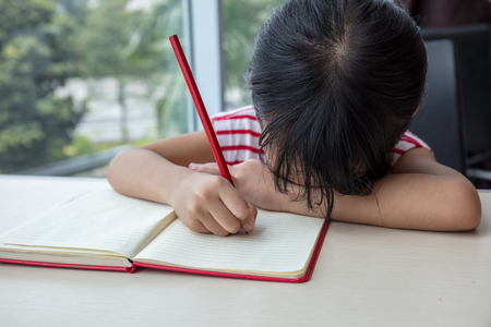 doze: Boring asian little Chinese girl writing homework at home