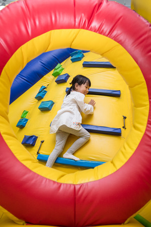 Asian Little Chinese Girl climbing up ramp at Indoor Playground