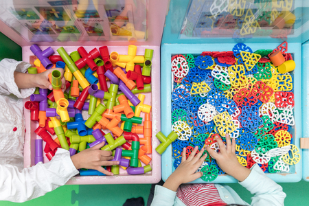 connection connections: Asian Little Chinese Girls playing puzzle at Indoor Playground Stock Photo