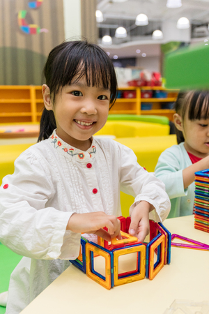 connection connections: Asian Chinese little girls playing colorful magnet plastic blocks kit at indoor playground