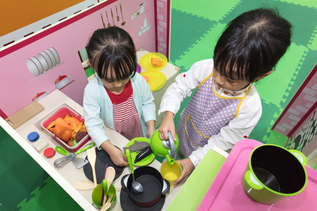 Asian Chinese little girls role-playing at kitchen at indoor playground