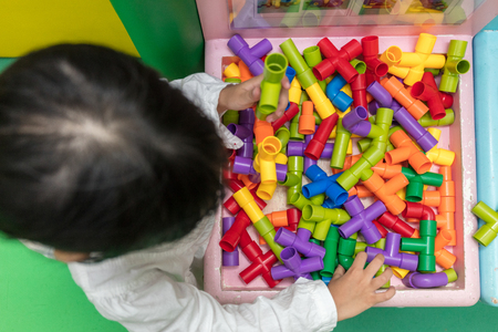 connection connections: Asian Little Chinese Girl playing puzzle tube at Indoor Playground Stock Photo
