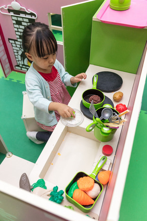 Asian Chinese little girl role-playing at kitchen at indoor playground
