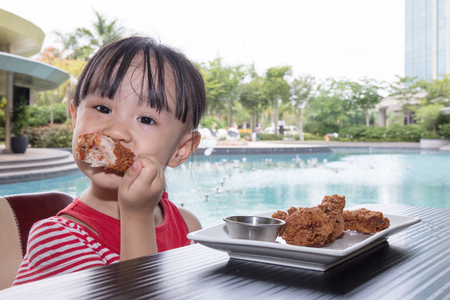 Asian Little Chinese Girl Eating Fried chicken at Outdoor Cafe