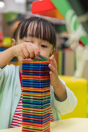 connection connections: Asian Chinese little girl playing colorful magnet plastic blocks kit at indoor playground