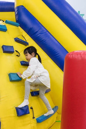 Asian Little Chinese Girl climbing up ramp at Indoor Playground Banco de Imagens