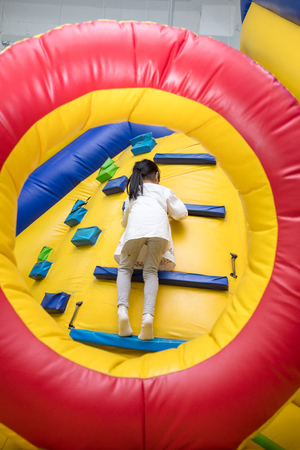 Asian Little Chinese Girl climbing up ramp at Indoor Playground Imagens