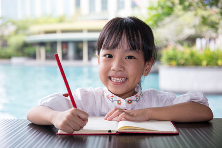 Asian Chinese little girl doing homework at outdoor cafe