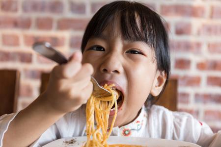 Asian Chinese little girl eating spaghetti bolognese in the restaurant