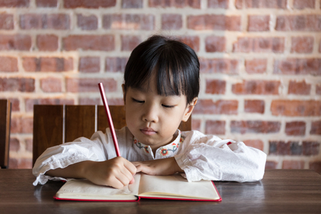 Asian Chinese little girl doing homework at indoor cafe Stock Photo