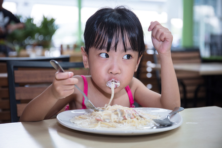 Asian Chinese little girl eating spaghetti at outdoor cafe Banco de Imagens