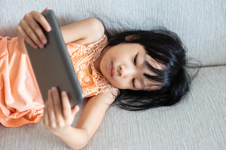 Asian Chinese little girl using tablet lying on the sofa in the living room 写真素材