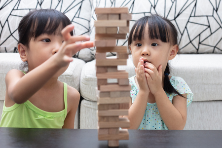 Asian Chinese little sisters playing wooden stacks at home Stockfoto