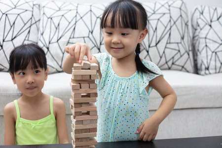 Asian Chinese little sisters playing wooden stacks at home 스톡 콘텐츠